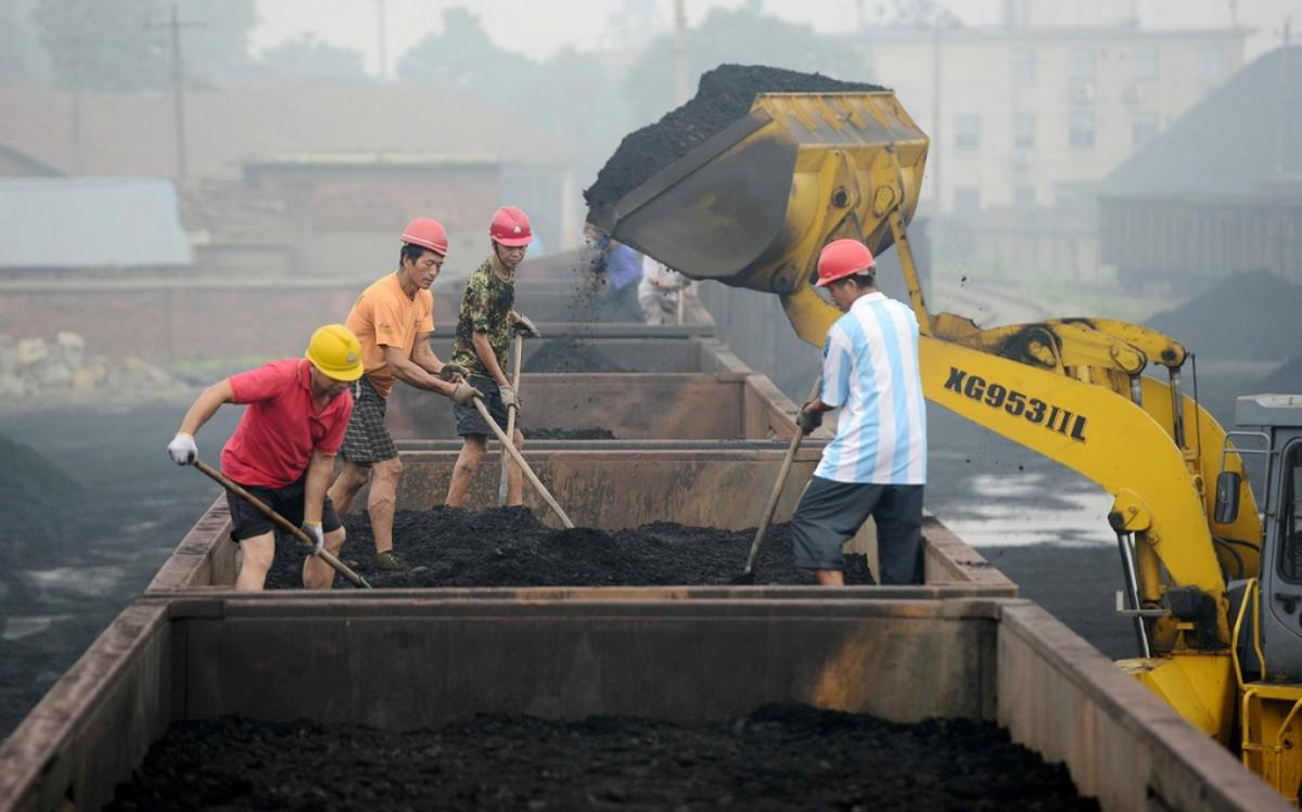Chinese workers level coal to be used for generating electricity on a freight train at a railway station in Jiujiang city on June 16, 2014. Imaginechina via AP Images